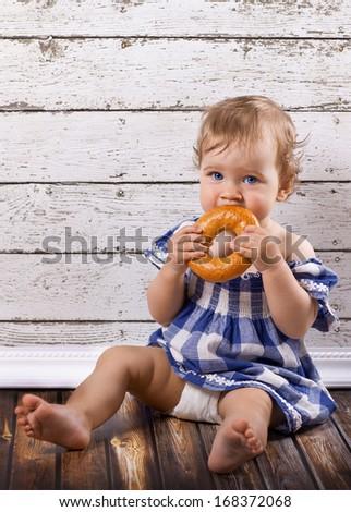 Cute kid sitting on the floor with the steering wheel