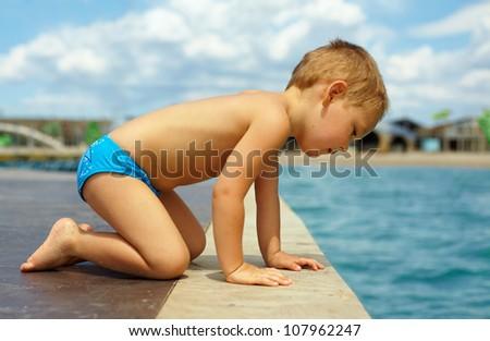 cute kid squats on pier, looks in water