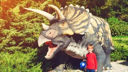 Cute kid walking in dinosaur park. Tourist attraction for children. Happy child having fun at dino park. Summer camp, vacation and weekend day.