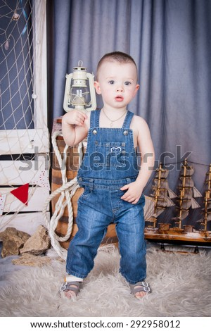 Cute kid with big gray eyes in denim overalls playing among the maritime decor.Handsome boy looking curiously into the frame.Handsome boy looking curiously into the frame.