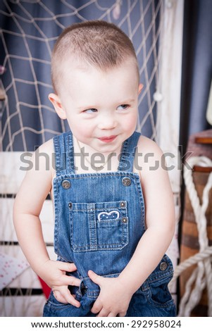 Cute kid with big gray eyes in denim overalls playing among the maritime decor.Handsome boy looking curiously into the frame.Handsome boy looking curiously into the frame. Boy hesitate.