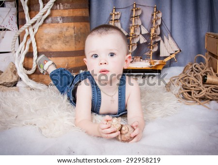 Cute kid with big gray eyes in denim overalls playing among the maritime decor.Handsome boy looking curiously into the frame.Handsome boy looking curiously into the frame. boy lying on the skin