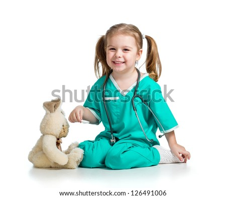 cute kid with clothes of doctor playing with plush toy over white - stock photo