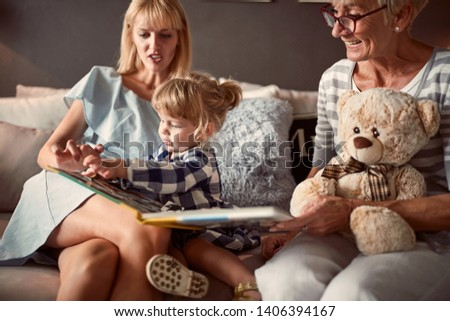 Cute kid with mother and grandma looking at picture book