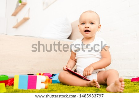 Cute kid with opened mouth sitting on green floor with construction and holding digital device #1485933797