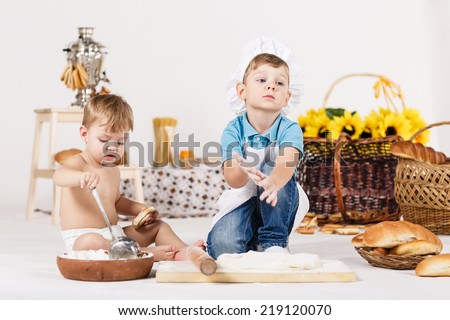 Cute kids, adorable little girl and funny boy wearing chef hats playing with dough baking a pie in a sunny white kitchen