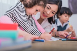 Cute kids and Asian teacher drawing in artist class. Back to school and education concept. Nursery and Preschool theme. Student and Baby sister theme.