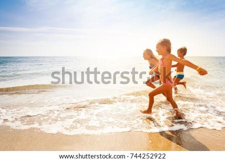 Cute kids having fun on sandy beach in summer