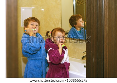 7f733660d1 Cute kids in bathrobes in the bathroom brushing their teeth  1038555175