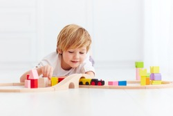 cute kids playing with toy railway road at home