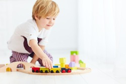 cute kids playing with toy railway road at home. focus on train