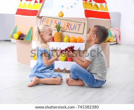 Stock Photo Cute kids sitting near counter with fruits indoors