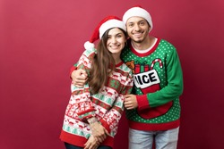 Cute Latin couple wearing ugly sweaters and hugging each other while getting ready for Christmas in a studio