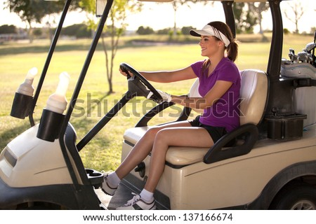 Cute Latin female golfer driving to the next hole in a golf course