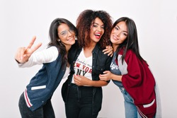 Cute latin girl in blue jacket posing with peace sign while relaxing with friends. Stunning curly african lady laughing and embracing international university mates.