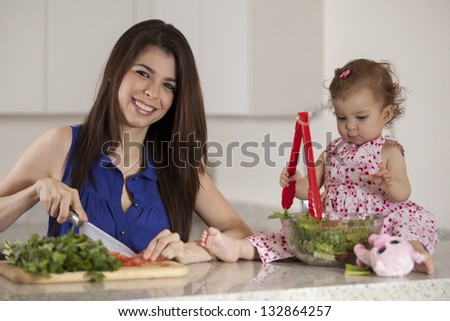 Cute latin mother cooking dinner while her baby girl sits on the counter