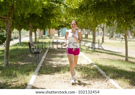 Cute latin woman running at the park
