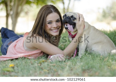 Cute latin woman spending some time with her pug dog at the park