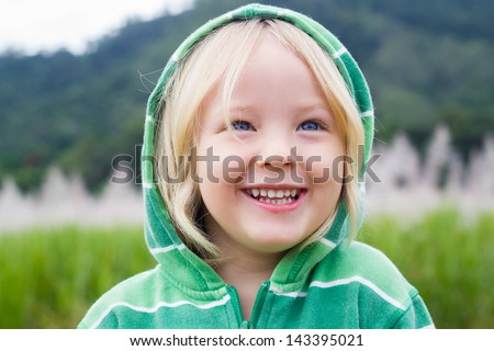 Cute laughing child in a green hoodie, standing in a sugar cane field