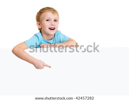 Cute laughing little boy is above on a white blank poster and points on it.