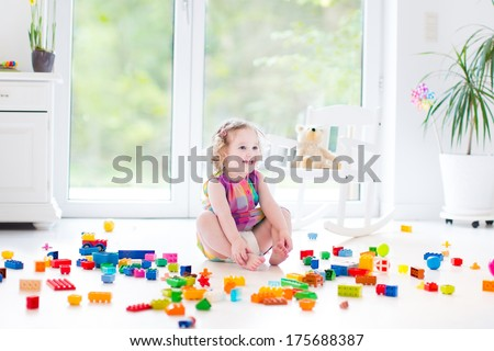 Cute laughing toddler girl playing with colorful blocks sitting on a floor in a sunny bedroom with a big window