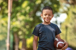 Cute little African-American boy with rugby ball in park