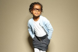 Cute little African American girl against light wall. Fashion concept