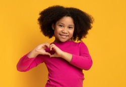 Cute little african american girl making heart shape with her hands and smiling to camera, posing over yellow background in studio, empty space