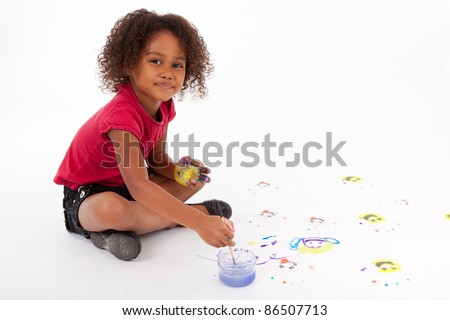 Cute Little African American girl painting on the floor