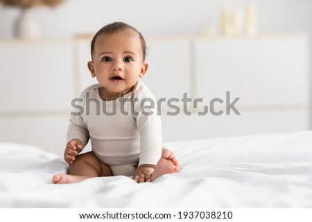 Cute little African American infant sitting on bed