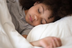 Cute little african american kid girl sleeping well alone in bed under warm blanket duvet lying on comfort white soft pillow, adorable small child rest asleep enjoy good healthy peaceful sleep or nap