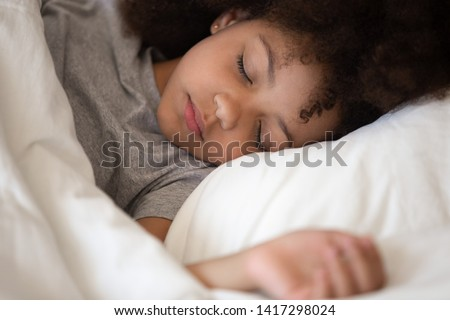 Photo of Cute little african american kid girl sleeping well alone in bed under warm blanket duvet lying on comfort white soft pillow, adorable small child rest asleep enjoy good healthy peaceful sleep or nap