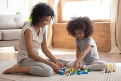 Cute little african american kid playing with black mom or baby sitter on floor, happy family mixed race mother helping small preschool child girl building constructor castle of wooden blocks at home