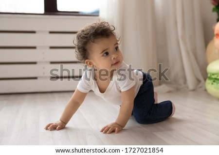 Photo of  Cute little african American toddler infant go on hands and knees learn to walk on floor at home, small biracial baby girl child creep on fours, make first steps play indoor, childcare concept