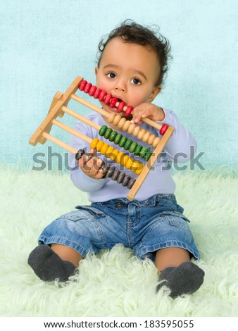 Cute little African baby boy playing with an abacus