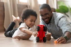 Cute little african kid son play toy cars with black dad, happy family small mixed race son and loving young father babysitter having fun racing on warm floor at home, family daddy child leisure game
