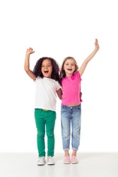 Cute little Afro American and caucasian girls are keeping hands up, looking at camera and smiling, isolated on a white background