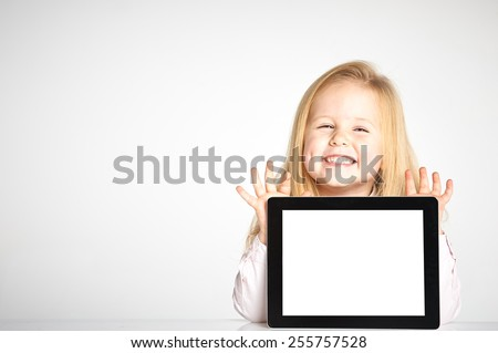 Cute little and smiling girl plays with a tablet #255757528