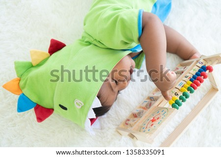 cute little asian baby boy lying and play toy #1358335091