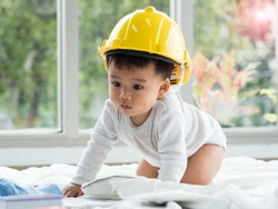 Cute little Asian baby boy wearing yellow hard hat crawling on white blanket in the living room at home.