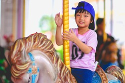 Cute little asian boy enjoying in funfair and riding on colorful carousel house and Waved hand and looking at camera with smile