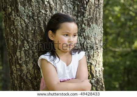 Cute little Asian girl in a white and pink dress, pouting by tree