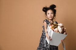Cute little asian girl in beautiful spring dress holds a big basket of big white flowers pion and looks up at somebody on green background