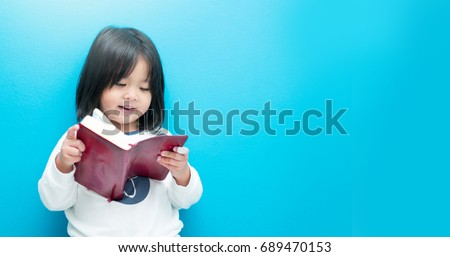 Cute little asian girl in pajamas reading bible before sleep.Hands holding on a Holy Bible in bed room concept for faith, spirituality and religion.blue background.