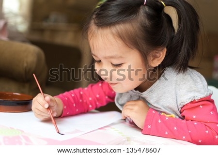 Cute little Asian girl learns to paint with her watercolors