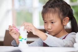 Cute little asian girl student painting a ceramic pottery model  in classroom school . kid artist . child sitting at desk preschool . Early education . Children in kindergarten.