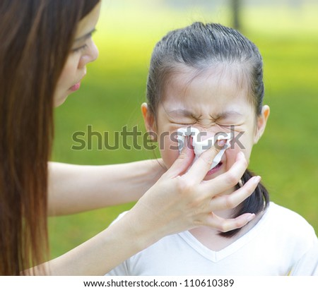 Cute little Asian girl with the flu, outdoor park