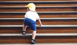 Cute little Asian 18 months / 1.7 year old toddler baby boy child climbs up the wooden stairs with the Mind your step sticker sign. Kid trying to walk up staircase concept.