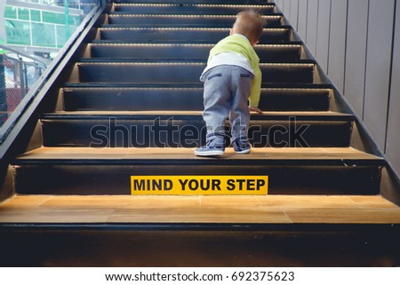 Cute little Asian 18 months / 1 year old toddler baby boy child climbs up the wooden stairs with the Mind your step sticker sign. Kid trying to walk up staircase - Selective focus at kid's shoes