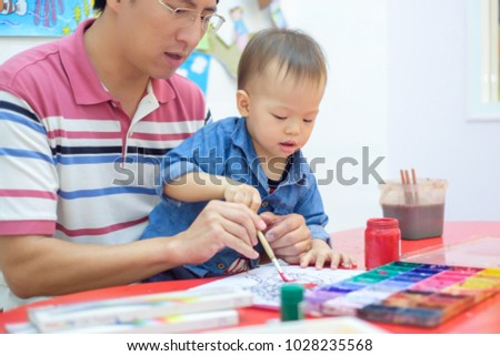 Cute little Asian 18 months / 1 year old toddler baby boy child painting with brush and watercolors, kid painting with father at home ,Creative play for toddlers concept